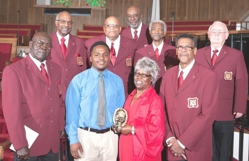 SHAD Club President Anthony Bell (back row-fourth from left) presented the 2013 winning plaque and cash award to DeShawn Redden (center front), whose stated career goal  is to be a teacher and to be active in the community. He has already demonstrated community support by helping to mentor young disadvantaged children. DeShawn was joined by Mrs. Faye Jackson, (center) wife of Mr. Samuel Jackson in whose memory the plaque is given.  They are surrounded by other members of SHAD Club #62 including Vice President Bobby Magby 1, who stands beside Mrs. Jackson on the right.