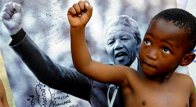 A young member of the Matibolo Cultural Troupe poses in front of a poster of Nelson Mandela during celebrations for the anti-apartheid leader's birthday. (AP Photo/Ben Curtis)