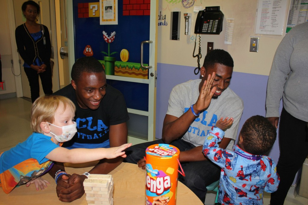 UCLA Bruins football players Aaron Sharp (left) and Jordan Lasley (right) play with patients Kaiden Cressy, 2, (left) and Jhordan Moncrief, 2 on Thursday, July 31.