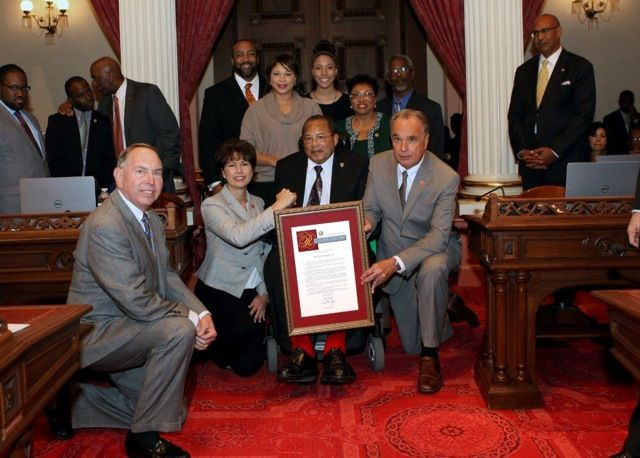 Hardy Brown is honored on the floor of the California State Senate. Included in this photo from left to right: (back row) son-in-law and Stockton City Manager Kurt Wilson, granddaughter Kennedy Wilson, brother Vince Brown; (middle row) daughter and California Black Media chair Regina Brown Wilson, wife Assemblymember Cheryl Brown (D-San Bernardino); (front row) Senator Richard Roth (D-Riverside), Senator Connie Leyva (D-Chino), Hardy Brown, and Senator Mike Morrell (R-Rancho Cucamonga).