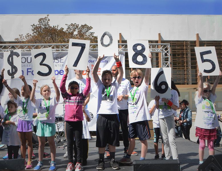 Children raise signs at the Run for Hope fundraiser for the Best Dollars Raised. Photo by Vivien