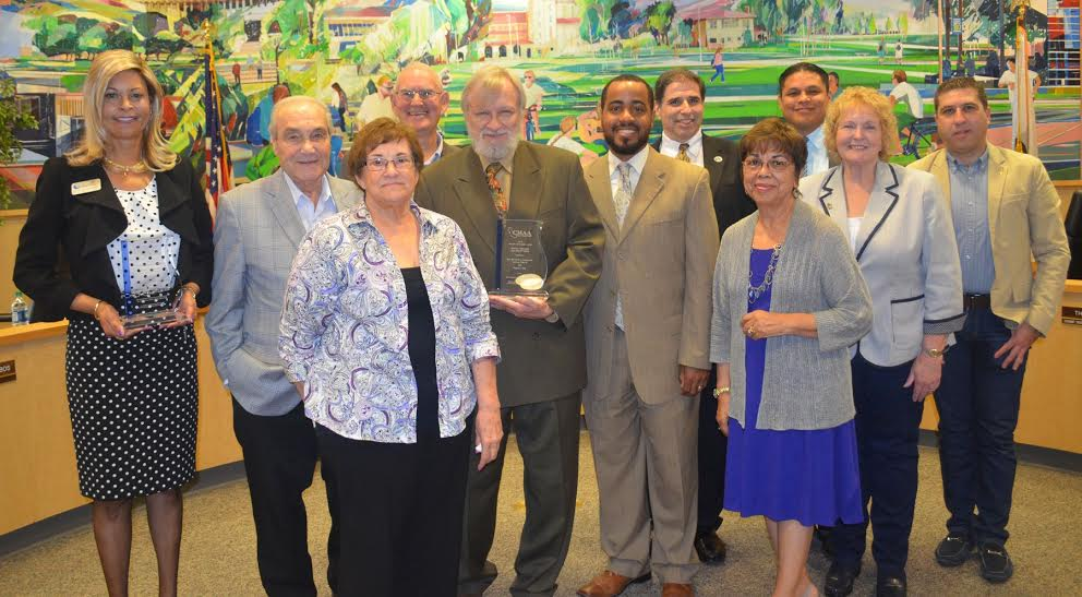 Front row: Dr. Gloria Fisher, President of SBVC (holding SBVC award); Nickolas Zoumbos, Trustee; Donna Ferracone, Trustee; Board President John Longville (holding SBCCD award); Board Clerk Joseph Williams; Gloria Macías Harrison, Trustee; and Board Vice President Dr. Kathleen (Katy) Henry. Back row: Dr. Donald Singer, Trustee; Chancellor Bruce Baron; Interim Vice Chancellor, Fiscal and Business Services Jose Torres; and Hussain Agah, Kitchell BRj Senior Campus Manager.