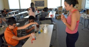 Monica Wilhelmus, assistant professor of mechanical engineering and chemical and environmental engineering, assists participants performing an experiment at a STEM workshop for middle and high school students hosted by