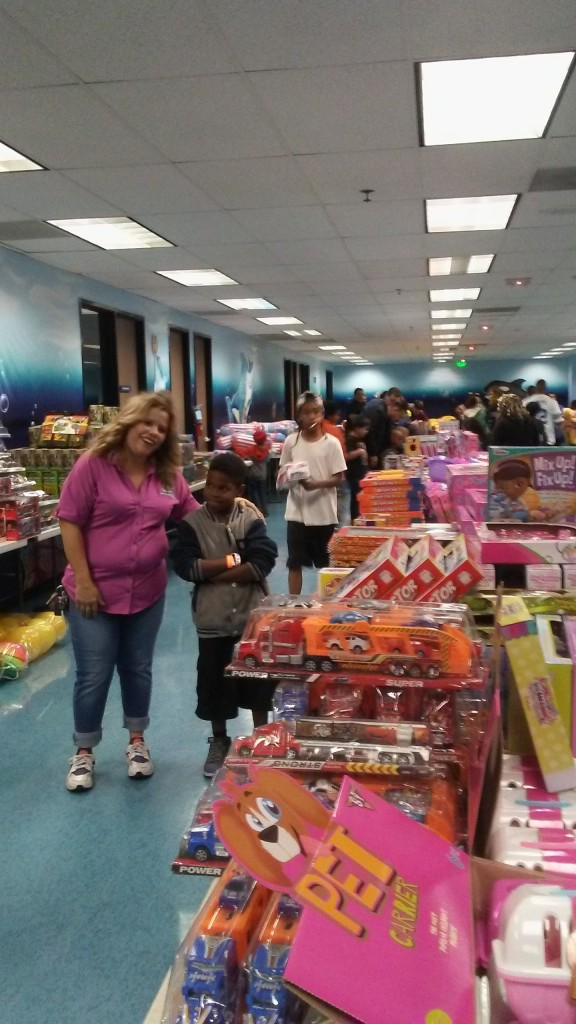 The Way World Outreach held its 12th annual Christmas present giveaway at its Hallmark campus on Sunday evening, where over 2,000 youth received a gift of their choosing.  Pictured is The Way World Outreach Children's Pastor Susan Zavala with Jovonn Taylor, 9. (Photo credit MJ Duncan)