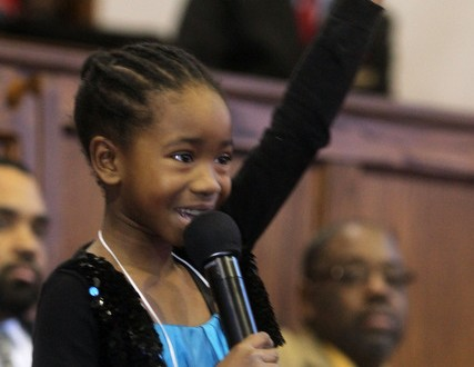 Sara Bartlett, 8, raises her fist to drive home a point as she delivers a speech during the13th Annual Dr. Martin Luther King Jr. Oratorical Contest at the Shiloh Baptist Church of New Rochelle Jan. 15, 2012. Children, ages 8-15 took part in the contest, in which contestants wrote their own speeches and presented them before judges and congregants. ( Seth Harrison/The Journal News )