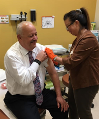 CSUSB President, Tomás D. Morales, receives his flu shot from Palm Desert Campus' family nurse practitioner, Cecile Dahlquist. (Photo Credit:  Albert Angelo)