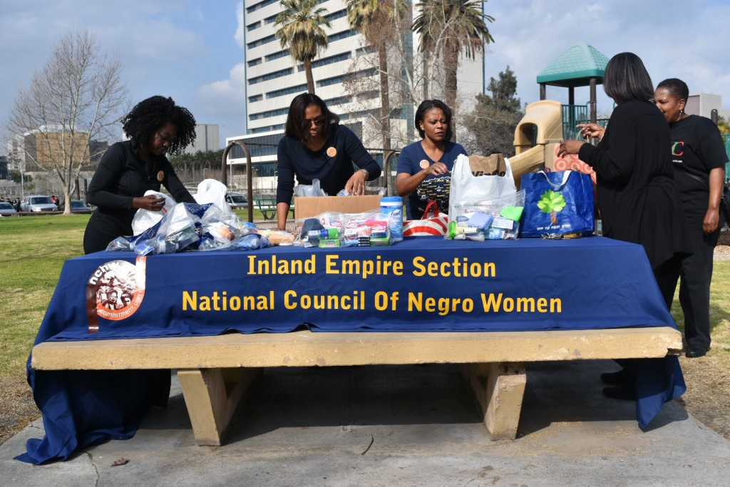 Members of NCNW prepare table a Meadowbrook Park to deliver care packets to the homeless.
