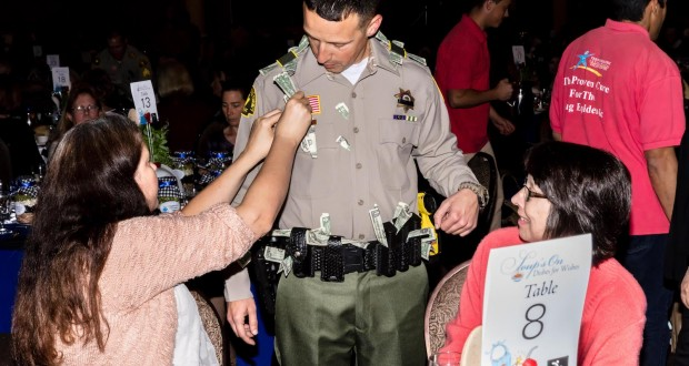 A San Bernardino County Sheriff deputy collects tips while serving dinner at Dishes for Wishes in 2016.