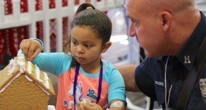 LLUCH patient, Makaylie Guerrero, 5, of Desert Hot Springs, got a helping hand from Nate Boucher of the Loma Linda Fire Department during the gingerbread village event on Monday, December 4.