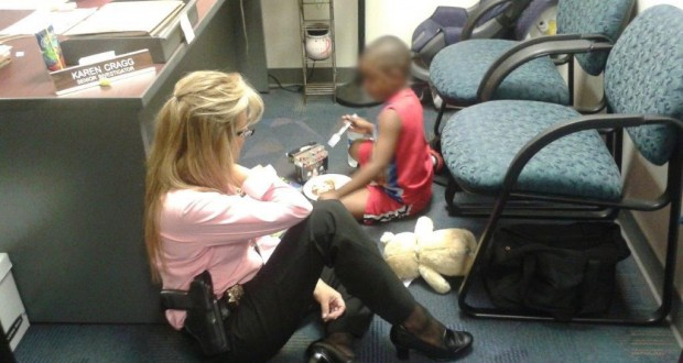 District Attorney Investigator Karen Cragg and the young boy play games and color with crayons while waiting for the father to arrive at the DA's Office.